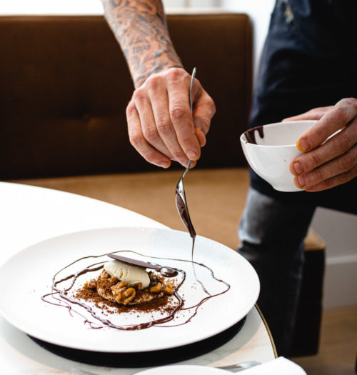A chef poring chocolate of a dessert on a white plate