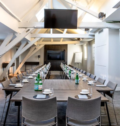 A bright meeting room with a long table and grey chairs in Pillows Hotel Reylof in Ghent