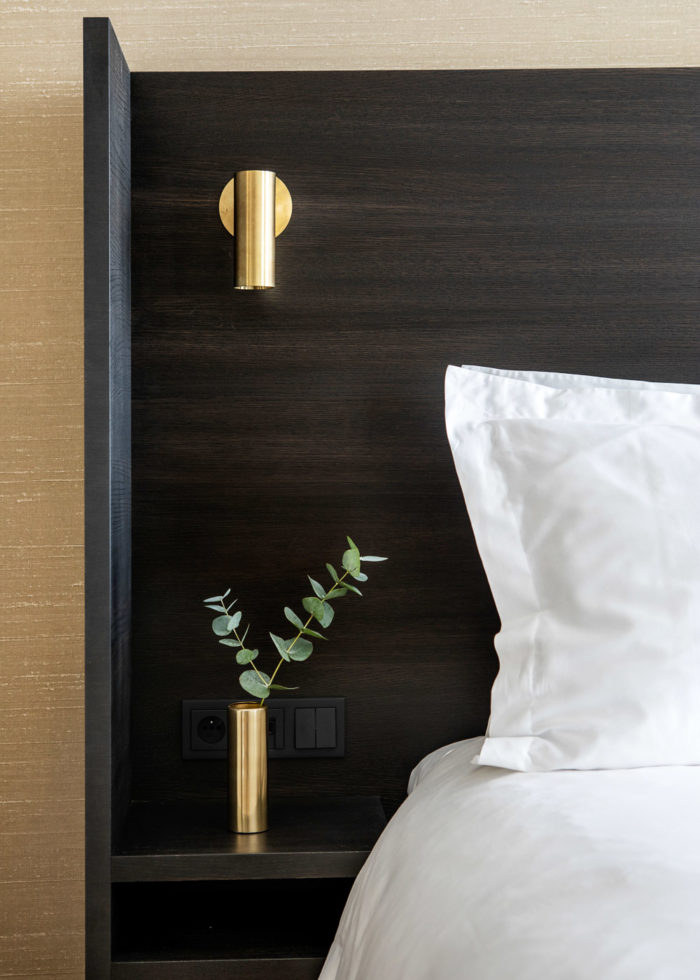 A small brass vase next to a bed with white linnen
