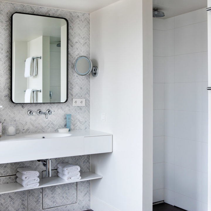 A hotel bathroom with grey tiles and a square mirror